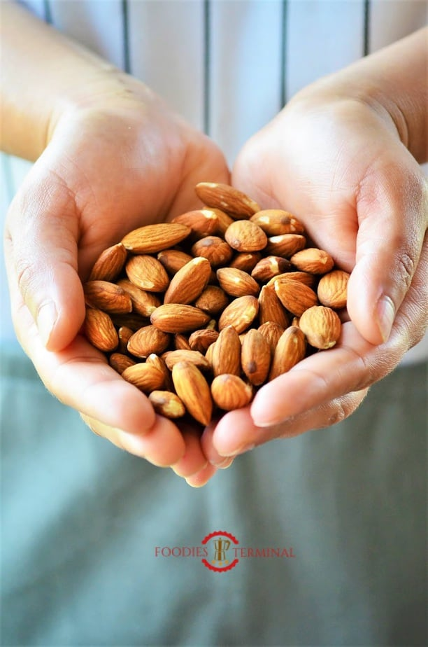 Raw almonds held in both hands