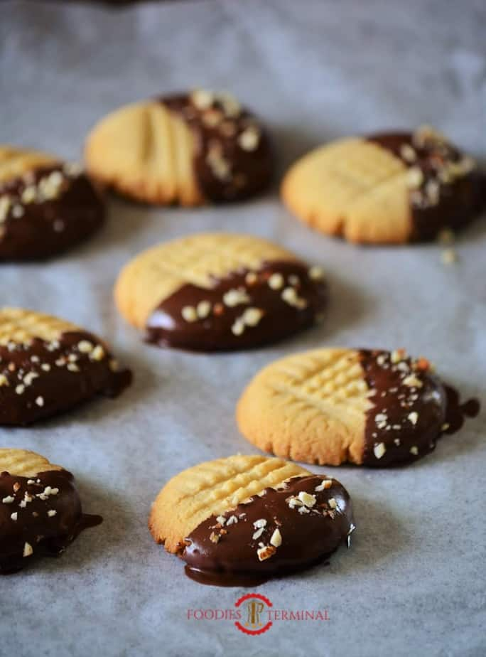 Shortbread cookies dipped in chocolate sauce and placed on the cookie tray.