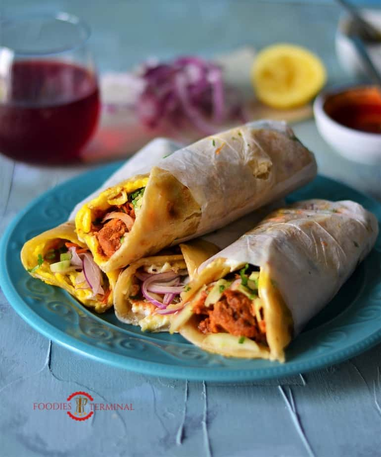 Four Chicken Kathi Roll plated over a dinner plate.