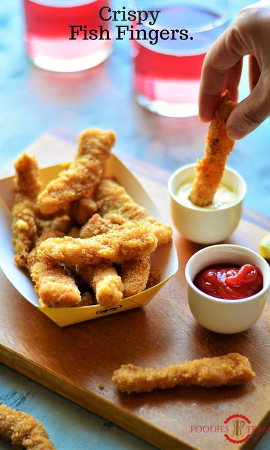 Basket full of fish fingers and one of them dipped in a sauce.