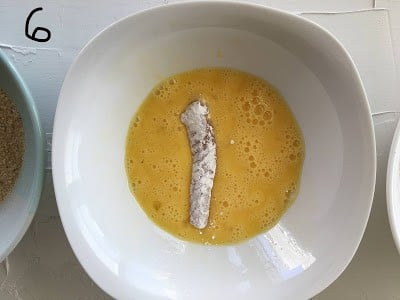 The flour coated fish dipped in beaten egg.