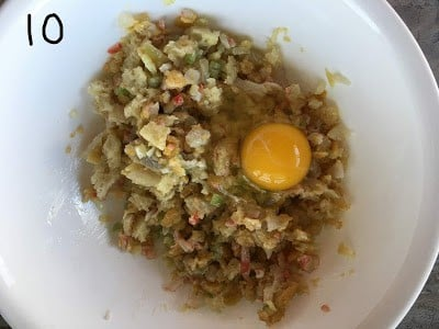 Egg added to the chopped crab meat, bread, celery & fish mixture.