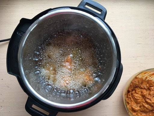 The marinated chicken pieces being fried in Instant Pot for the chicken 65 recipe