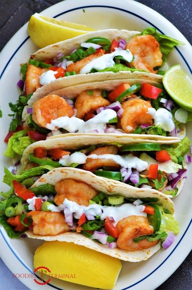 Cajun Shrimp Tacos garnished with sour cream sauce