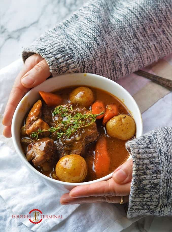 Hands holding a bowl of lamb stew cooked in Instant Pot