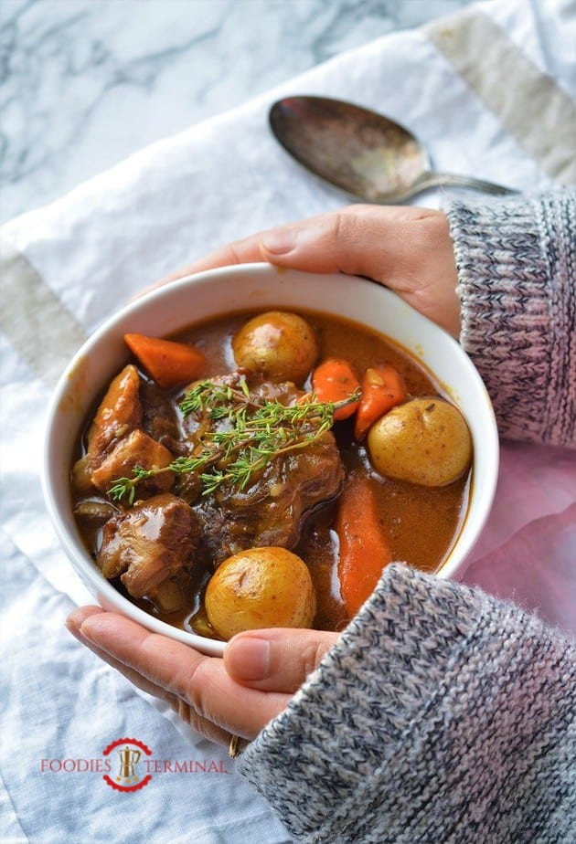 Hands holding a warm bowl of Lamb stew