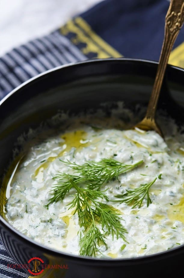 Best Tzatziki Sauce Recipe garnished with dill in a black bowl