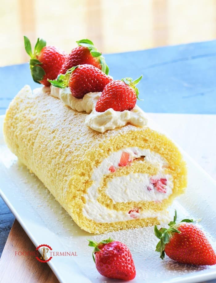 Vanilla Swiss Roll Cake Recipe topped with strawberries