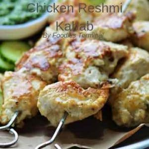 chicken reshmi kabab skewered in metal skewers