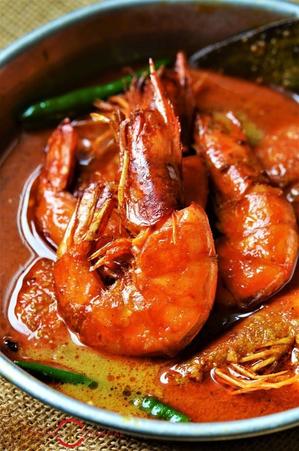 Chingri Macher malai curry featuring a huge tiger prawn in a red sauce with green chilies