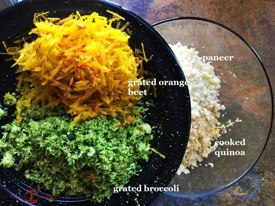 Quinoa patties ingredients grated broccoli & grated orange beet on a black plate