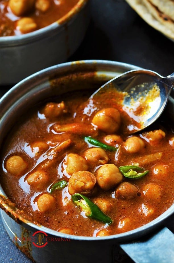 Instant Pot chana masala in a red sauce with a spoon