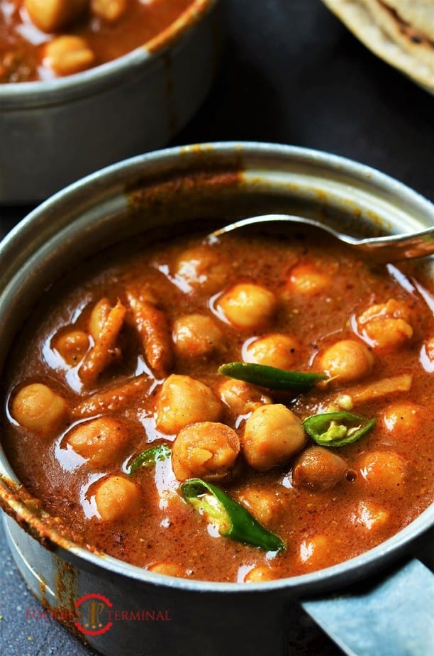 Instant Pot Punjabi Chole served in a pot garnished with chilies