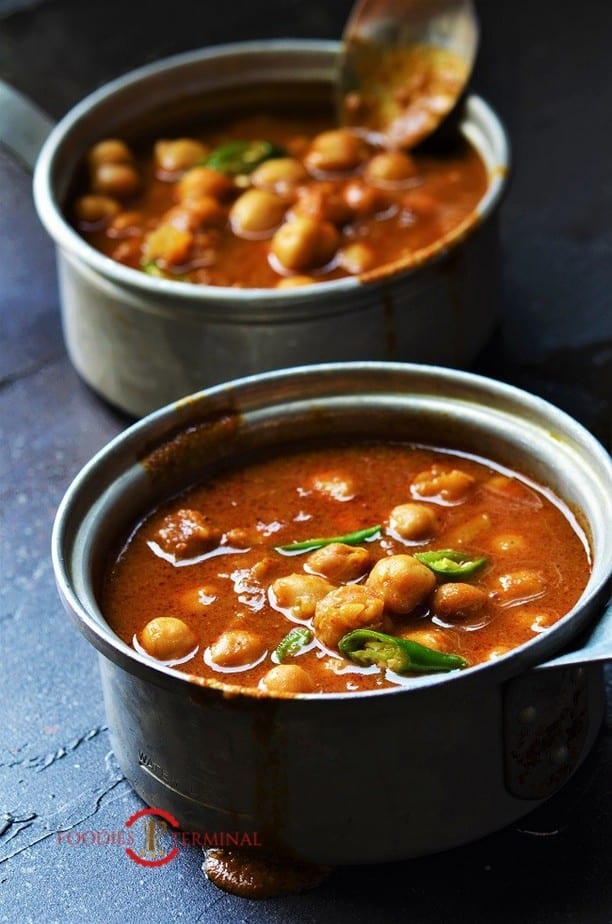 Instant Pot Chana Masala in two aluminum pots with a spoon