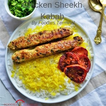 Chicken seekh kabab served over a bed of turmeric rice
