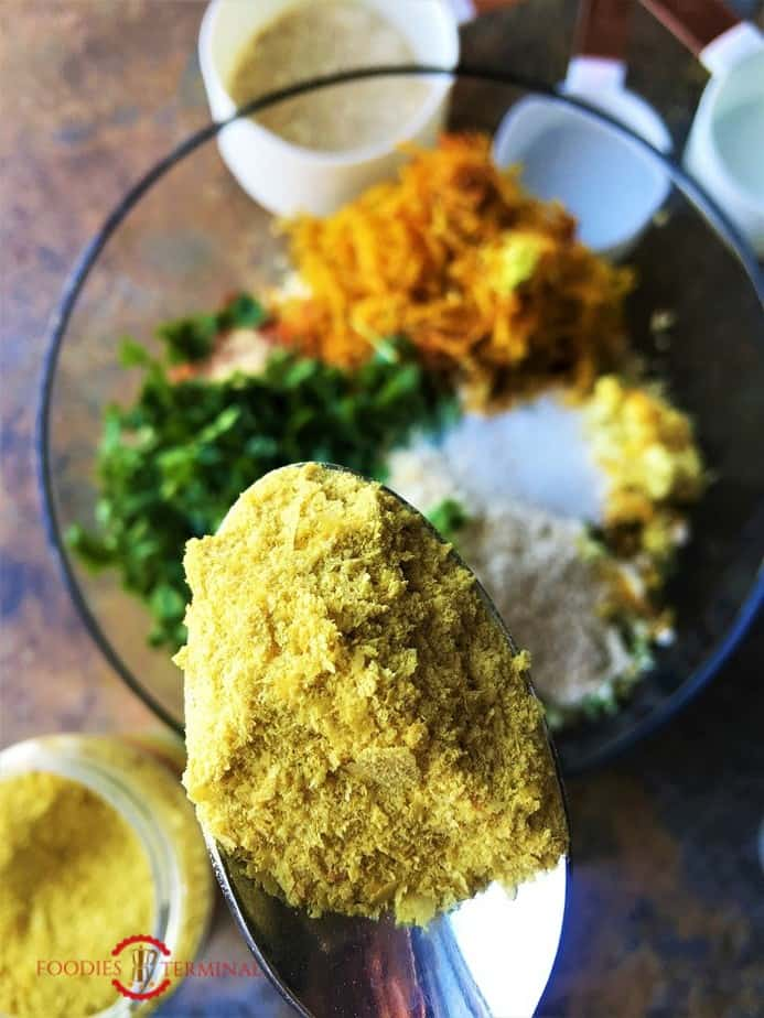 Nutritional yeast being added to the dough of quinoa paneer cutlets