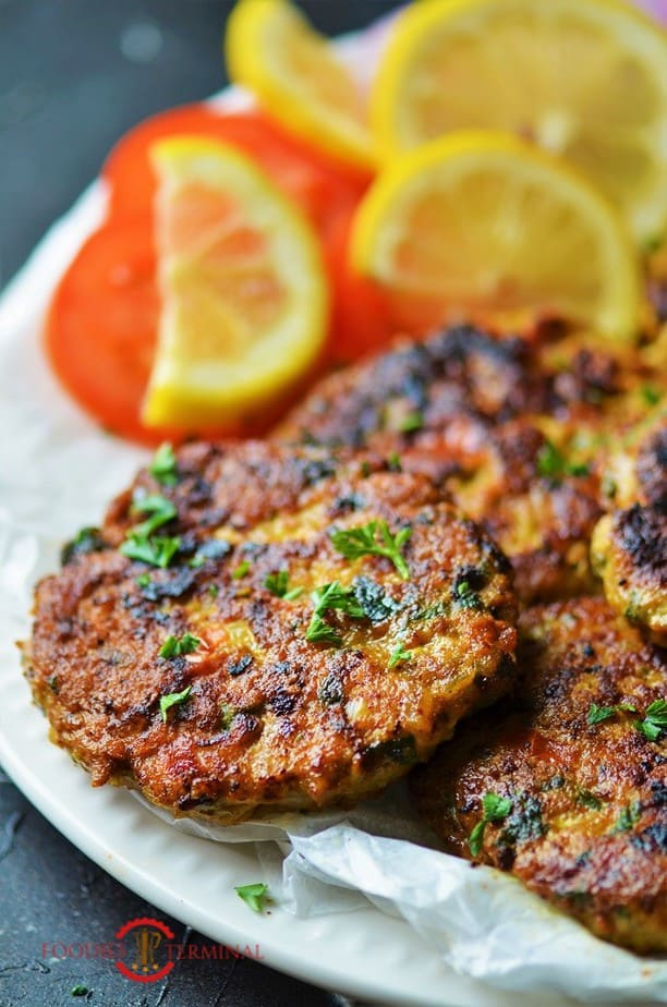 chicken chapli kabab on a white plate garnished with cilantro
