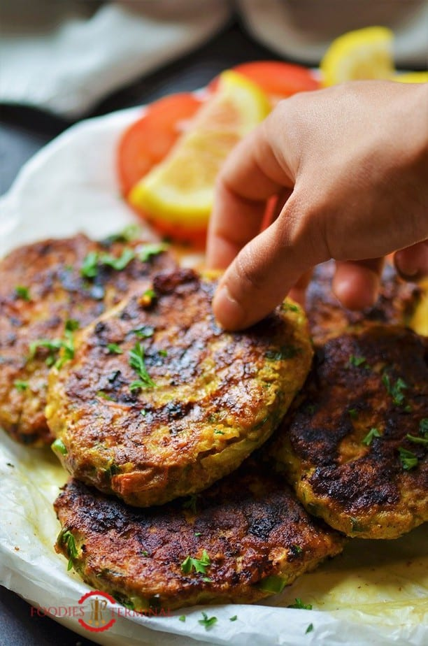 Chicken Chapli Kabab stacked together & being lifted