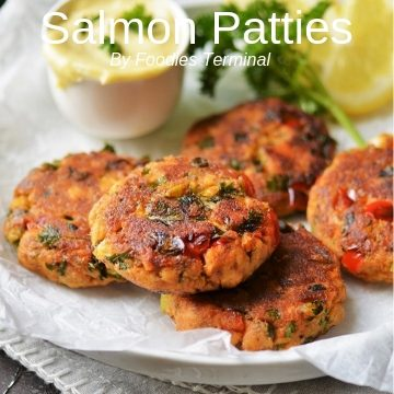 Salmon patties stacked on a white plate