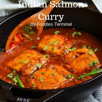 Indian Salmon curry in an iron wol with a wooden spatula