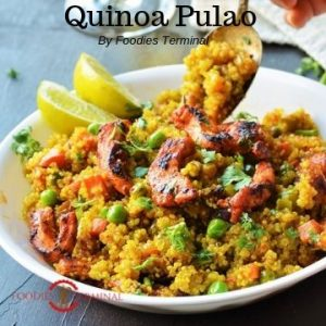 Quinoa Pulao served in a white bowl with lemon wedges