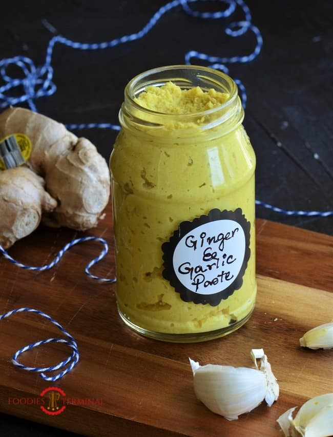 Homemade Ginger Garlic Paste recipe in a bottle on wood board