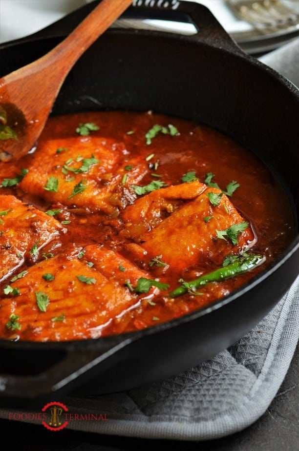 Indian style Salmon curry garnishe with cilantro in a black wok