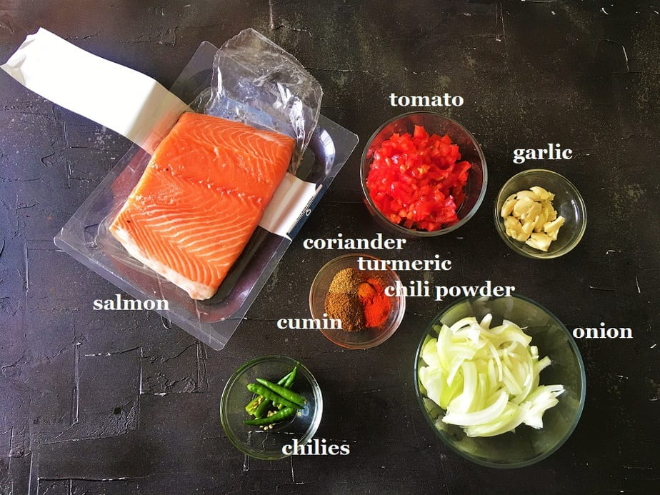 Ingredients for easy Salmon curry in various bowls on a black surface