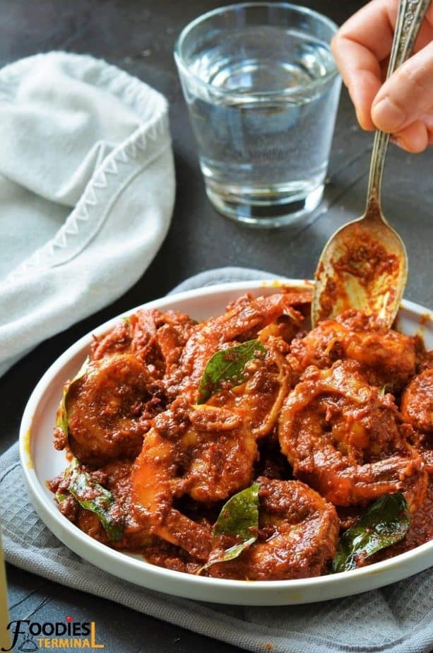 Prawn ghee roast Kundapur style on a white plate with a spoon