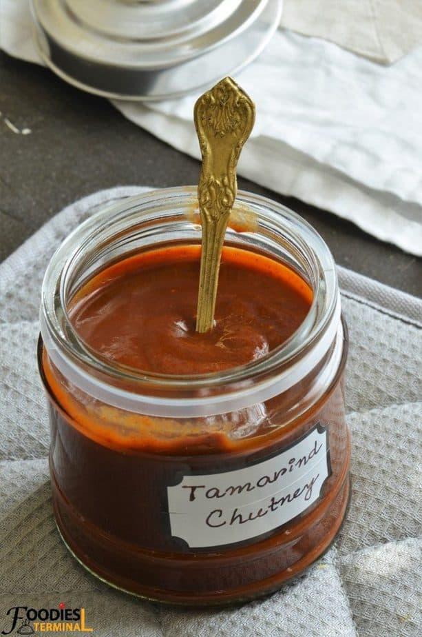 Khatti meethi tamarind chutney for samosa in a jar with a spoon
