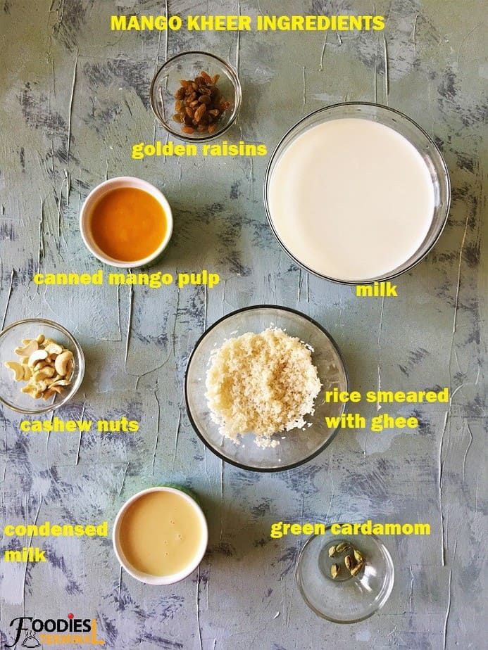 Mango kheer ingredients in bowls on a grey board