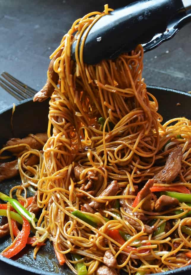 Stir fry chicken lo mein being lifted with a tong from pan