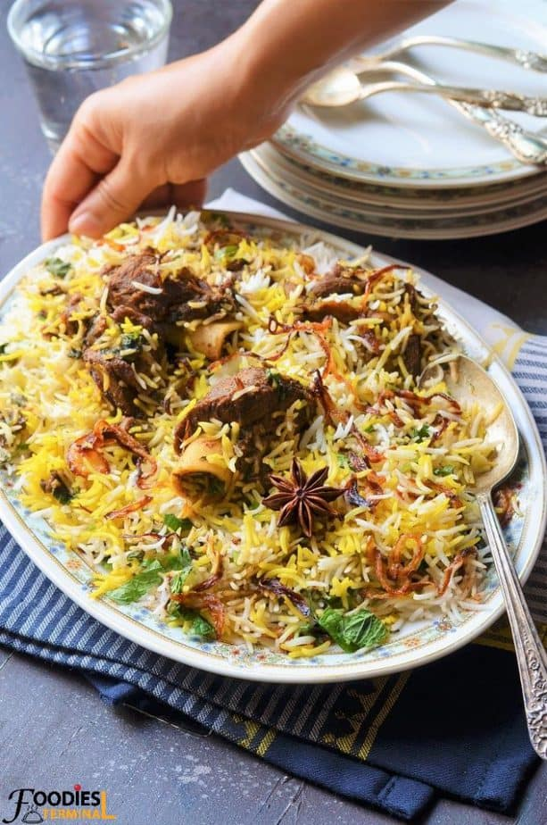 Homemade Mutton Biryani in an oval plate with mutton pieces & birista