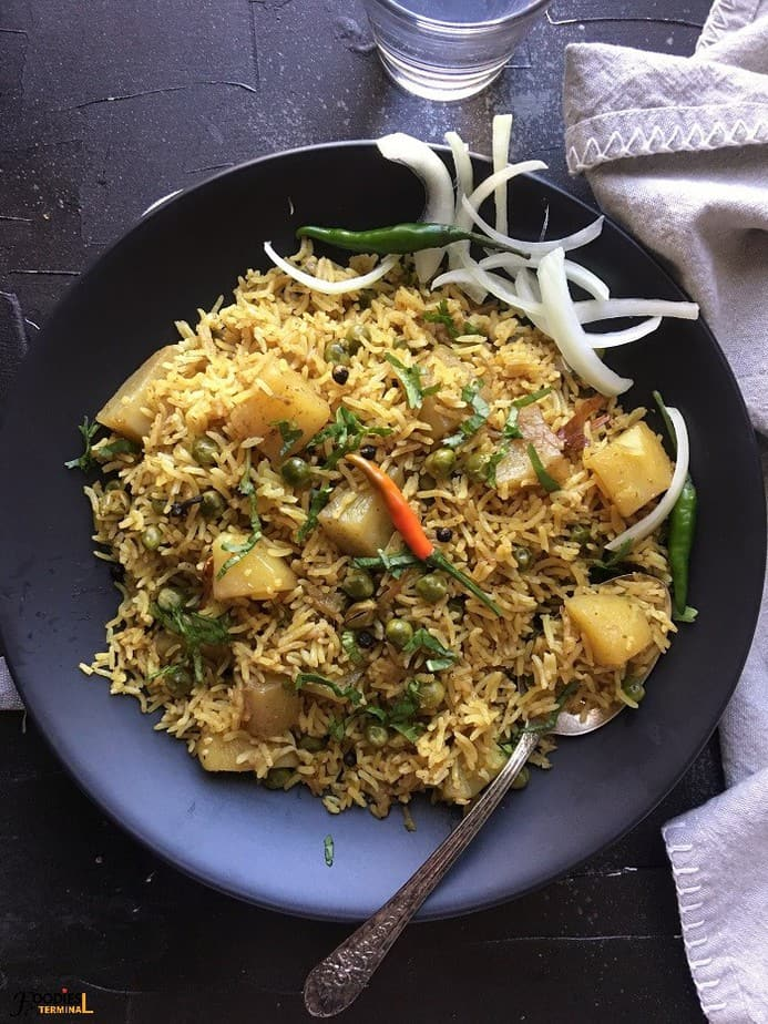 Instant Pot aloo mutter pulao served on a black plate with chilies & onion