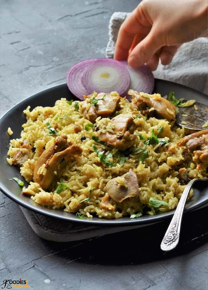 Pressure cooker chicken pulao on a plate with onion rings