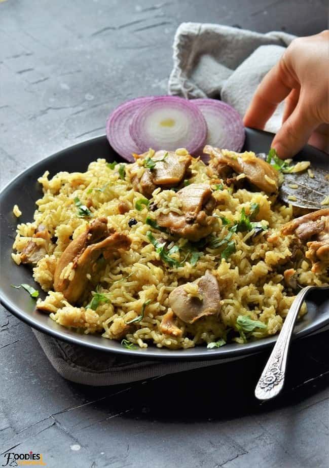 Chicken Pulao served with onions on a black plate