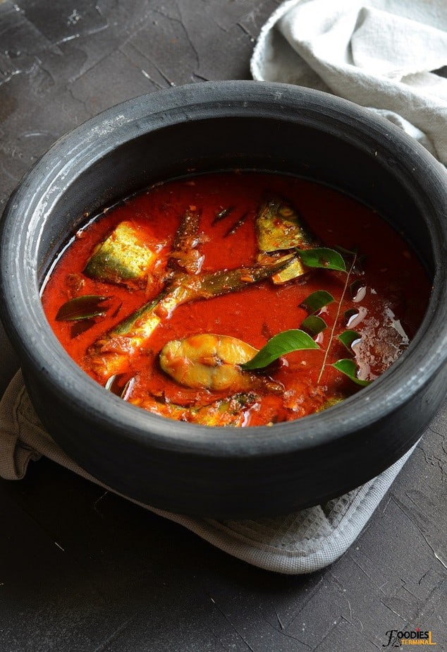 Kerala fish curry with coconut milk in a black earthen pot