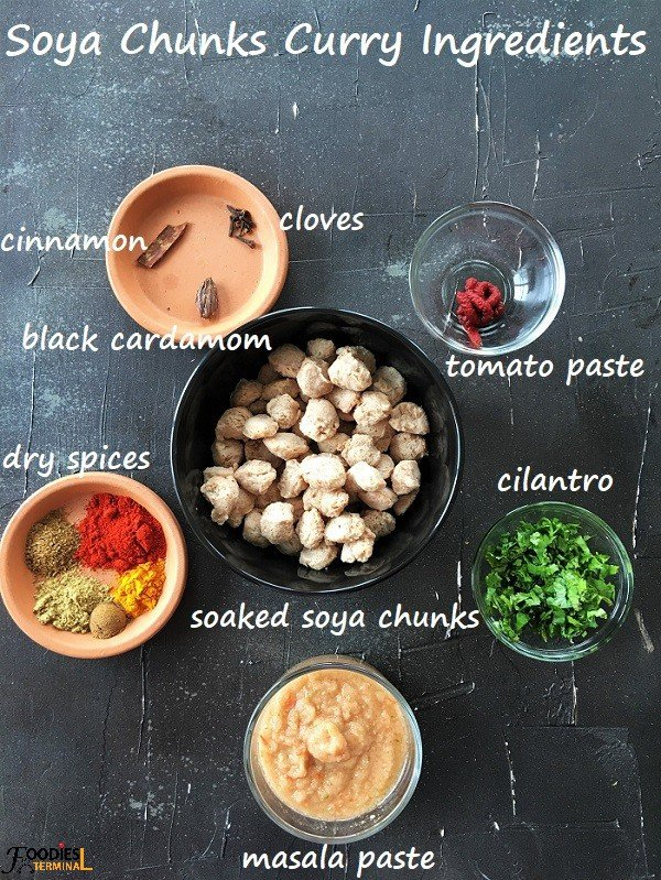 Nutrela Nuggets or soya bean curry ingredients in bowls on a black surface