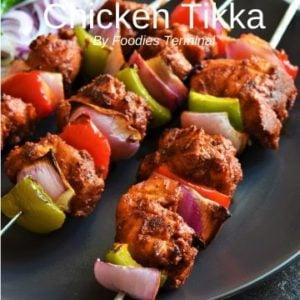 Chicken tikka in metal skewers with veggies