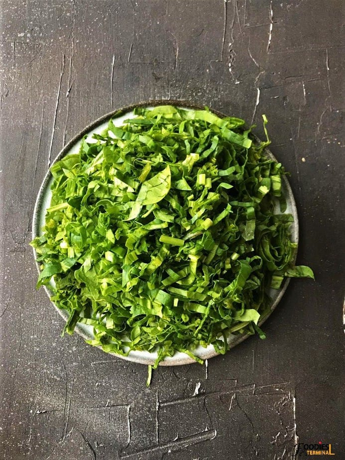 finely chopped spinach on a plate on a black surface