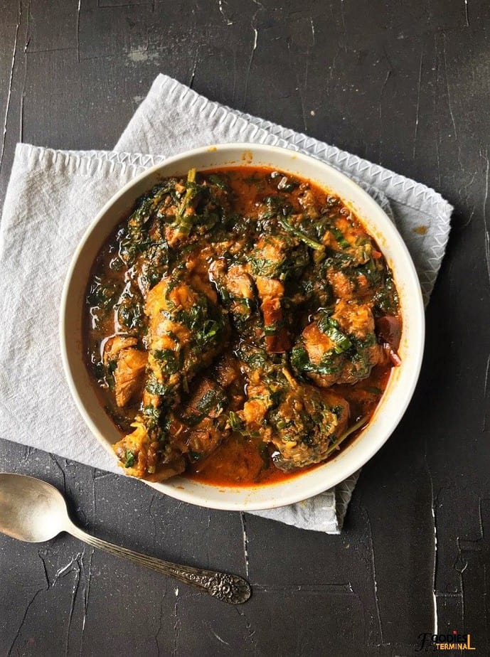 Homemade Palak Chicken restaurant style in a bowl with a spoon beside
