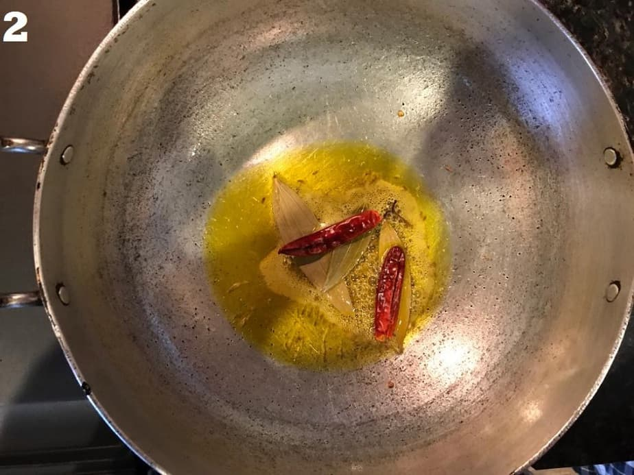 tempering oil in a kadai with cumin, red chilies and bay leaves