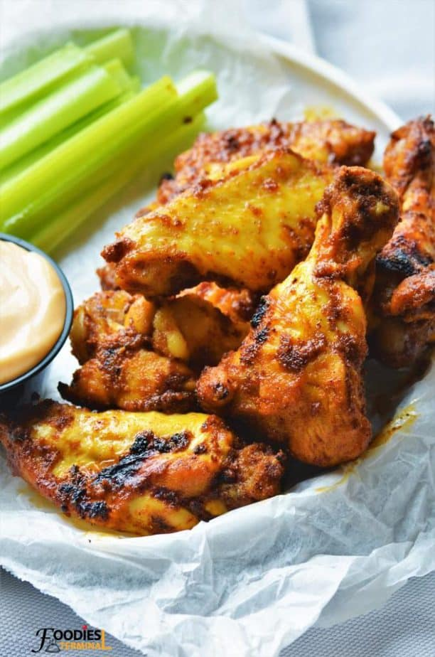 Tandoori wings served in a basket with sauce.