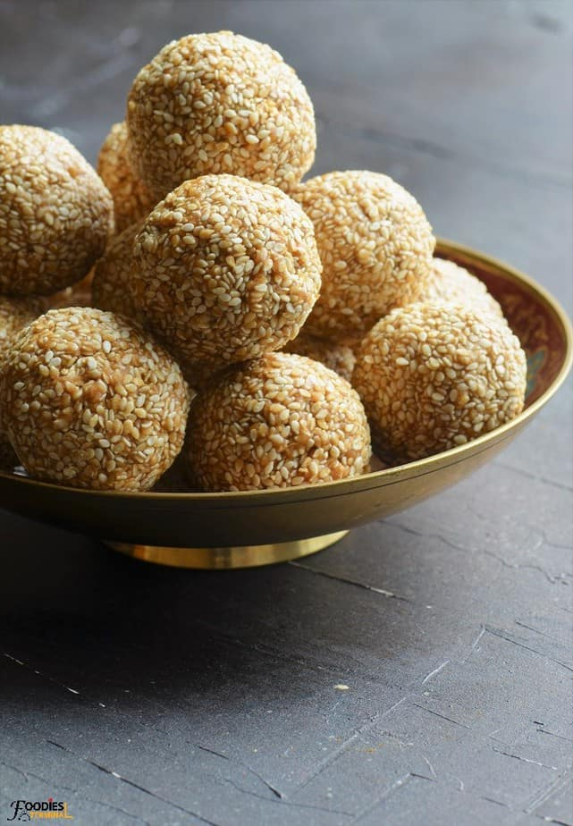 Sesame laddu in a gold bowl stacked on a pile