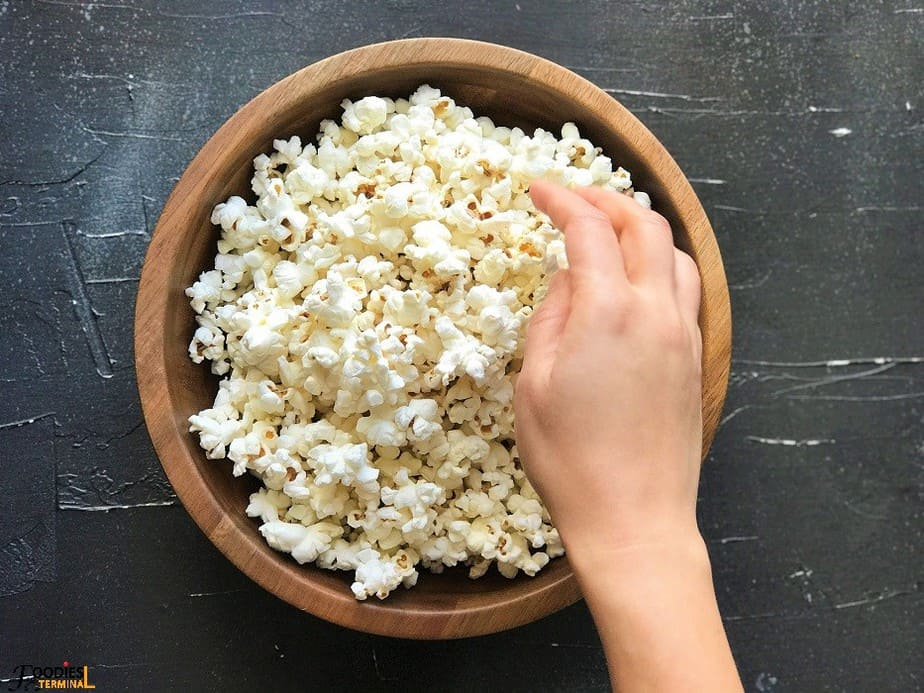 Instant pot kettle corn in a wooden bowl being arranged with hand