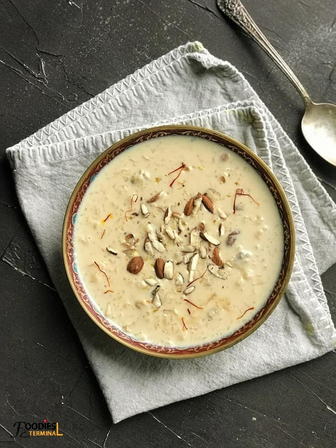 Instant Pot kheer in a brass bowl on a gray linen with a spoon beside