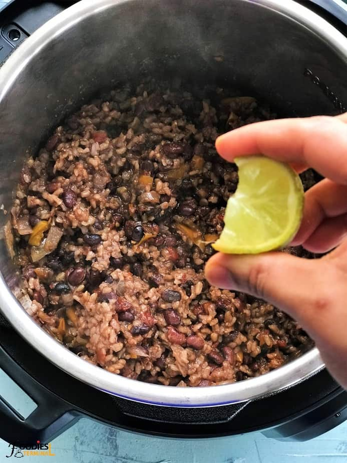 lemon juice squeezing on rice and black beans instant pot
