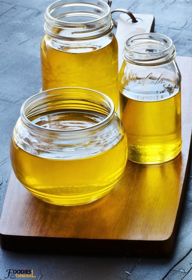 Instant pot ghee in three glass jars on a wood base