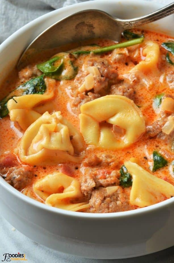 instant pot creamy tortellini soup with sausage and spinach with a spoon in a soup bowl