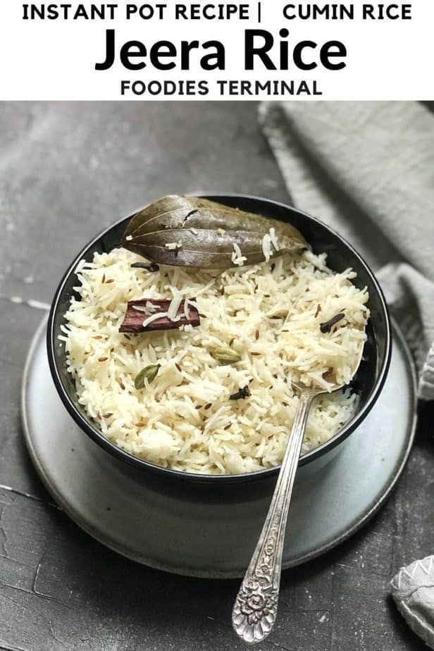 Instant Pot Jeera Rice in a black bowl on a gray plate served with a silver spoon